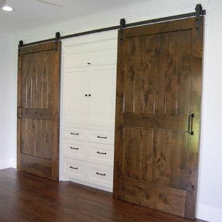 Imagen de armario unisex, campestre, pequeño, con armarios estilo shaker, puertas de armario blancas, suelo de madera oscura y suelo marrón