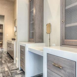Immagine di un grande spazio per vestirsi unisex chic con ante lisce, ante in legno chiaro e pavimento in marmo