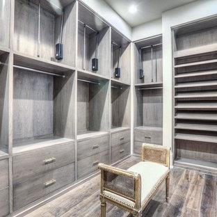 Großes, Neutrales Klassisches Ankleidezimmer mit Ankleidebereich, flächenbündigen Schrankfronten, braunem Holzboden und grauen Schränken in Houston