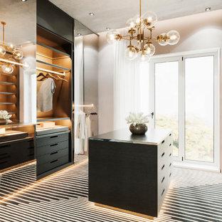 Ispirazione per una cabina armadio unisex design di medie dimensioni con ante di vetro, ante grigie, moquette e pavimento nero