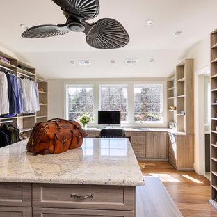 Modelo de armario vestidor unisex, de estilo de casa de campo, grande, con armarios abiertos, puertas de armario de madera clara, suelo de madera en tonos medios y suelo marrón