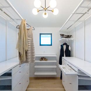На фото: большая гардеробная комната в стиле современная классика с белыми фасадами и светлым паркетным полом для женщин с