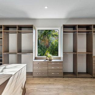 Ejemplo de armario y vestidor unisex, actual, con armarios abiertos, puertas de armario de madera oscura, suelo de madera en tonos medios y suelo marrón