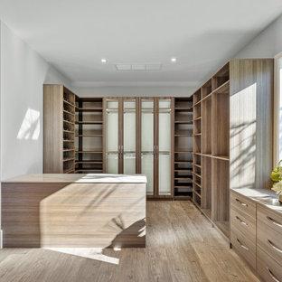Modelo de armario y vestidor unisex, actual, con armarios abiertos, puertas de armario de madera oscura, suelo de madera en tonos medios y suelo marrón