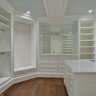 Imagen de armario vestidor de mujer, tradicional renovado, extra grande, con puertas de armario blancas, suelo de madera en tonos medios y armarios con paneles empotrados