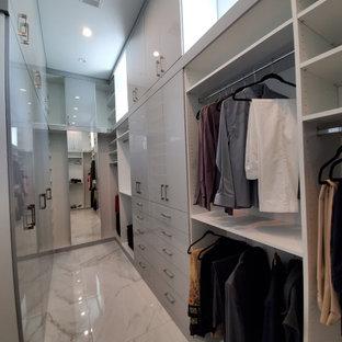 Réalisation d'un grand dressing minimaliste neutre avec un placard à porte plane, des portes de placard blanches, un sol en marbre et un sol blanc.