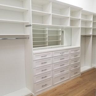 Inspiration för stora klassiska walk-in-closets för könsneutrala, med skåp i shakerstil, vita skåp, ljust trägolv och beiget golv