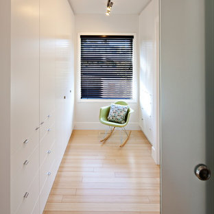 Photo of a small contemporary gender neutral walk-in wardrobe in Calgary with flat-panel cabinets, white cabinets, light hardwood flooring and beige floors.