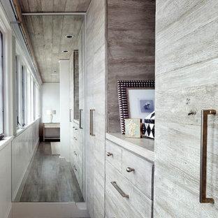 Ejemplo de armario vestidor unisex, marinero, de tamaño medio, con armarios con paneles lisos, puertas de armario de madera oscura y suelo de madera en tonos medios