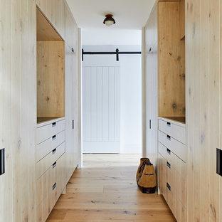 ニューヨークの男女兼用ビーチスタイルのおしゃれなウォークインクローゼット (フラットパネル扉のキャビネット、淡色木目調キャビネット、淡色無垢フローリング) の写真