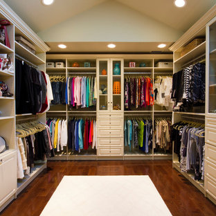 Example of a large classic women's dark wood floor walk-in closet design in New York with raised-panel cabinets and white cabinets