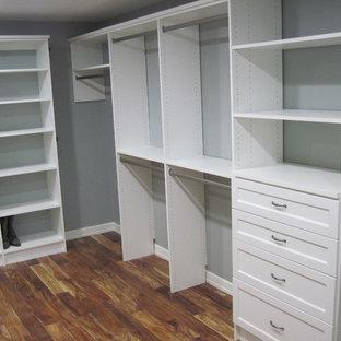 Imagen de armario vestidor unisex, clásico, de tamaño medio, con armarios abiertos, puertas de armario blancas y suelo de madera oscura