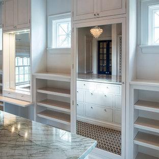 Foto di una grande cabina armadio unisex minimal con ante con bugna sagomata, ante bianche e pavimento marrone