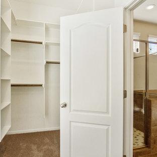 Ispirazione per una cabina armadio unisex mediterranea di medie dimensioni con moquette e pavimento beige