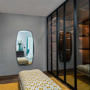 Foto di una cabina armadio unisex contemporanea di medie dimensioni con ante di vetro, ante nere, pavimento marrone e pavimento in legno massello medio