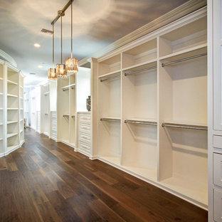 Ejemplo de armario vestidor unisex, clásico renovado, extra grande, con armarios con paneles con relieve, puertas de armario blancas y suelo de madera oscura