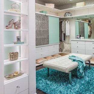 Ejemplo de vestidor de mujer, contemporáneo, de tamaño medio, con armarios con paneles lisos, puertas de armario blancas y suelo de madera oscura