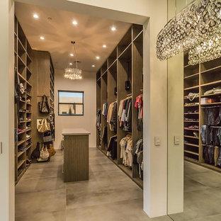 Imagen de armario vestidor unisex, contemporáneo, grande, con armarios con paneles lisos, puertas de armario de madera clara y suelo de cemento