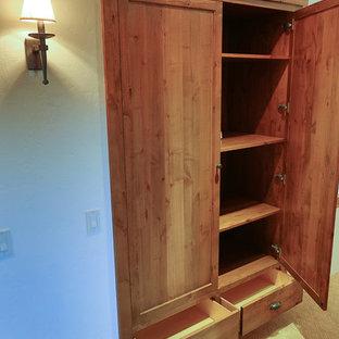 Immagine di un grande armadio o armadio a muro unisex classico con ante con riquadro incassato, ante in legno scuro e moquette