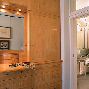 Design ideas for a mid-sized contemporary gender-neutral built-in wardrobe in New York with recessed-panel cabinets, light wood cabinets, marble floors and white floor.