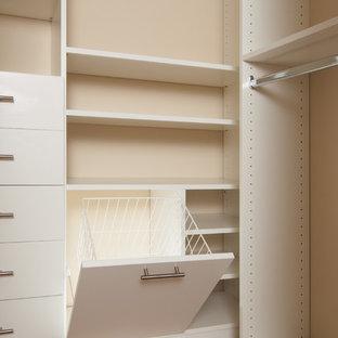 Immagine di una cabina armadio unisex minimalista di medie dimensioni con ante bianche, moquette e ante lisce