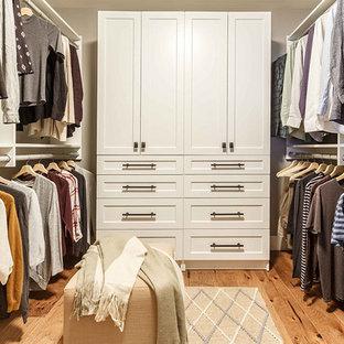 Immagine di una cabina armadio chic di medie dimensioni con ante con riquadro incassato, ante bianche, parquet chiaro e pavimento marrone