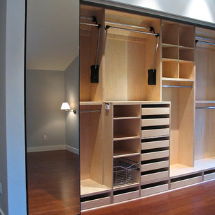 Example of a small minimalist gender-neutral dark wood floor reach-in closet design in Portland with open cabinets and light wood cabinets