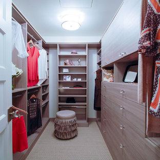 Diseño de armario vestidor de mujer, marinero, de tamaño medio, con armarios con paneles lisos, puertas de armario de madera clara y moqueta