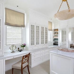Esempio di uno spazio per vestirsi chic con moquette, ante di vetro, ante bianche e pavimento beige