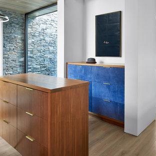 Esempio di un grande spazio per vestirsi unisex minimal con ante lisce, parquet chiaro, ante blu e pavimento beige