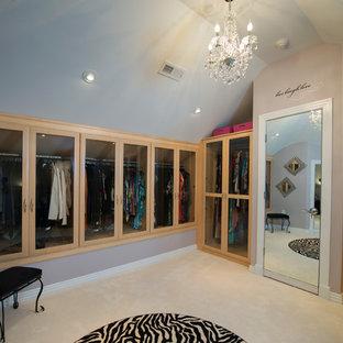 Immagine di un grande spazio per vestirsi per donna classico con ante di vetro, ante in legno chiaro e moquette