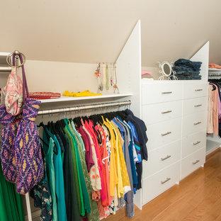 Klassisk inredning av ett mycket stort walk-in-closet för kvinnor, med öppna hyllor, vita skåp och brunt golv