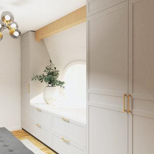 Ejemplo de vestidor unisex, vintage, de tamaño medio, con armarios con paneles empotrados, puertas de armario grises y suelo de madera clara