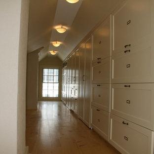 Foto di una piccola cabina armadio unisex tradizionale con ante bianche, pavimento in legno massello medio e ante con riquadro incassato
