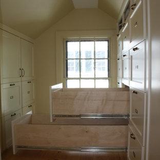 Foto de armario vestidor unisex, tradicional, pequeño, con armarios estilo shaker, puertas de armario blancas y suelo de madera en tonos medios