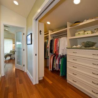 Réalisation d'un dressing tradition avec un placard avec porte à panneau encastré, des portes de placard blanches et un sol en bois brun.
