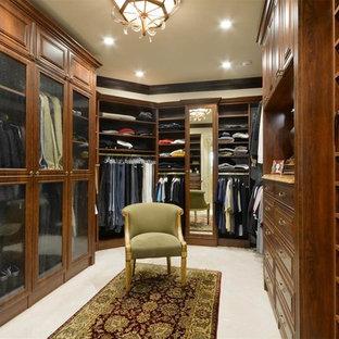 Ejemplo de armario vestidor de hombre, mediterráneo, de tamaño medio, con armarios con paneles con relieve, puertas de armario de madera en tonos medios, moqueta y suelo blanco