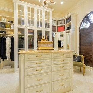 Modelo de armario vestidor de mujer, mediterráneo, grande, con armarios con paneles empotrados, puertas de armario de madera clara, suelo de mármol y suelo blanco
