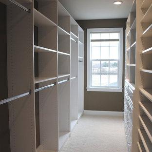 Modelo de armario vestidor clásico, de tamaño medio, con armarios con paneles con relieve, puertas de armario blancas y moqueta