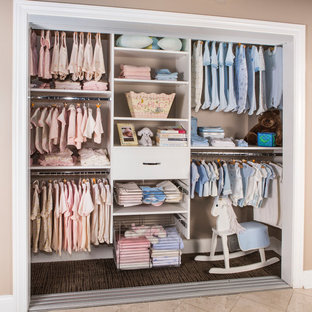 This is an example of a medium sized contemporary gender neutral standard wardrobe in Minneapolis with flat-panel cabinets, white cabinets, travertine flooring and beige floors.