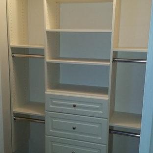 Diseño de armario unisex, tradicional, pequeño, con armarios con paneles con relieve, puertas de armario beige y suelo de madera en tonos medios