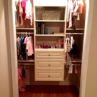 Ejemplo de armario unisex, clásico, pequeño, con armarios con paneles con relieve, puertas de armario beige y suelo de madera en tonos medios