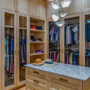 Idee per una cabina armadio per donna classica con ante di vetro, ante in legno chiaro, pavimento in legno massello medio e pavimento marrone