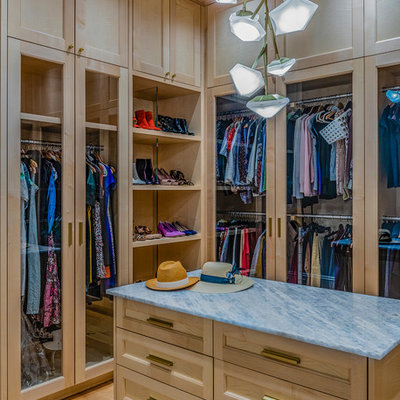 Walk-in closet - transitional women's medium tone wood floor and brown floor walk-in closet idea in Boston with glass-front cabinets and light wood cabinets