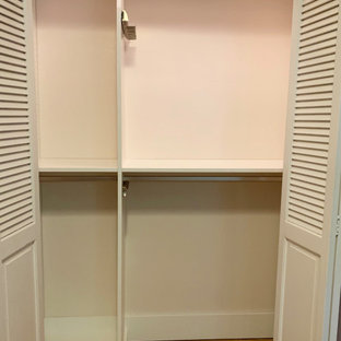 Foto de armario unisex, tradicional, pequeño, con armarios con paneles lisos, puertas de armario blancas, suelo de madera clara y suelo amarillo