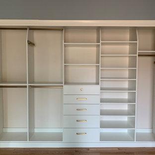 Modelo de armario unisex, clásico, pequeño, con armarios con paneles lisos, puertas de armario blancas, suelo de madera clara y suelo amarillo