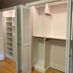 Ejemplo de armario unisex, tradicional, pequeño, con armarios con paneles lisos, puertas de armario blancas, suelo de madera clara y suelo amarillo