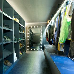 Industriell inredning av ett stort walk-in-closet för könsneutrala, med öppna hyllor, grå skåp och svart golv