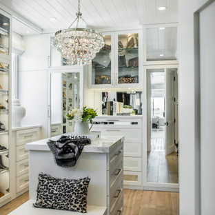Beach style women's walk-in wardrobe in Orange County with white cabinets and light hardwood floors.