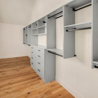 Diseño de armario vestidor unisex, campestre, extra grande, con puertas de armario grises, suelo de madera en tonos medios y suelo marrón